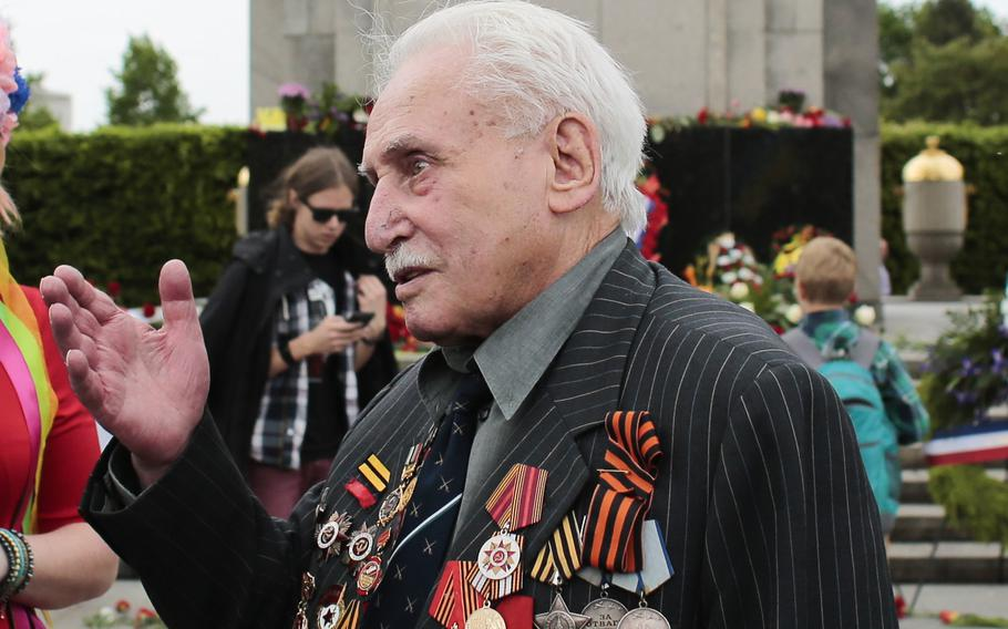 Soviet war veteran David Dushman, 92, center, speaks to people holding Ukrainian flags as he attends a wreath laying ceremony at the Russian War Memorial in the Tiergarten district of Berlin, Germany, on May 8, 2015. Dushman, the last surviving Allied soldier involved in the liberation of Auschwitz, has died.