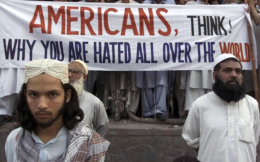 """Activists of Pakistan militant religious parties stand with a banner which reads, """"Americans, think why you are hated all over the world,"""" during a rally on Sept. 15, 2001, in Islamabad, Pakistan to condemn possible U.S. attacks on neighboring Afghanistan."""