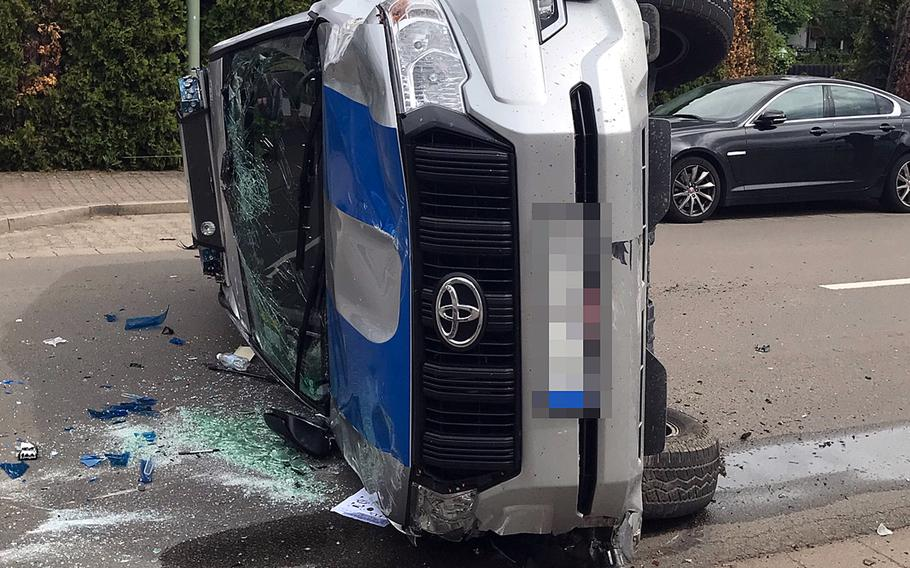 A military police vehicle sits on its side after the driver lost control, hit a parked car and then overturned, blocking Kaiserstrasse in Kaiserslautern, Germany, May 21, 2021, near Pulaski Barracks, local police said.  Police department Westpfalz
