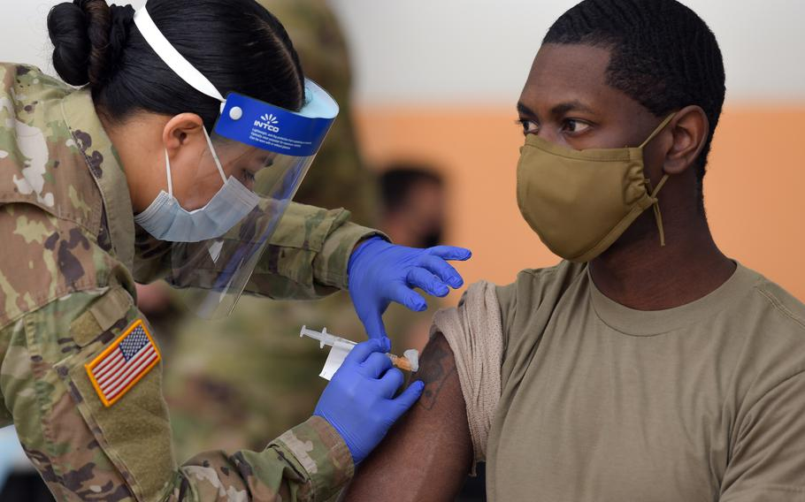 U.S. Army Spc. Eyza Carrasco, left, with the 2nd Cavalry Regiment, administers a COVID-19 vaccination at Rose Barracks in Vilseck, Germany, in May 2021.