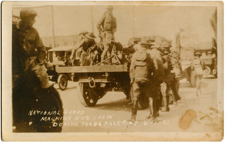 """This black-and-white photographic postcard titled """"National Guard Machine Gun Crew"""" shows a group of soldiers marching through Tulsa on June 1, 1921."""