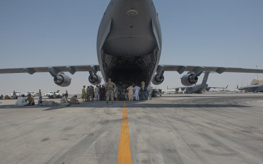Qualified evacuees wait on the flight line as they debark a C-17 Globemaster lll Aug. 20, 2021. As part of Operation Allies Refuge, Afghan citizens evacuated Hamid Karzai International Airport, Kabul, onboard military aircraft.