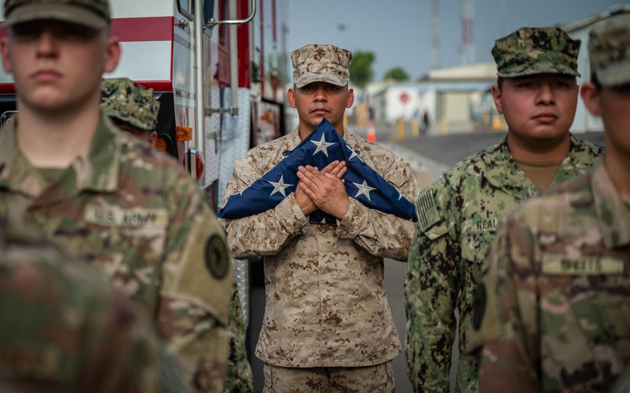 U.S. Marine Staff Sgt. Roberto Bravo, with Marine Air Refuel Transport Squadron 234, holds an American flag during a Patriot's Day ceremony at Camp Lemonnier, Djibouti, Sept. 11, 2021, commemorating the 20th anniversary of 9/11.
