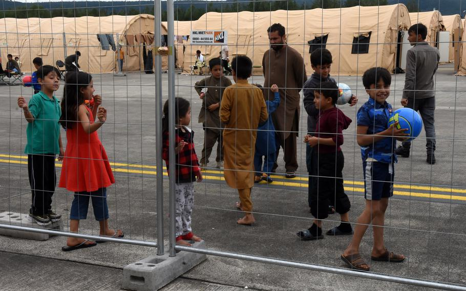 An Afghan boy flashes a smile Monday, Aug. 23, 2021, at Ramstein Air Base in Germany. Airmen handed children balls through the fence at the temporary living facilities for evacuees from Afghanistan.