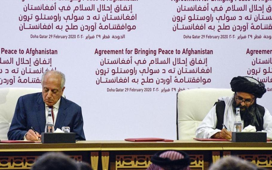 Zalmay Khalilzad, American special envoy for Afghan reconciliation, signs a peace deal with the Taliban, along with Mullah Abdul Ghani Baradar, the militant group's top political leader, in Doha, Qatar, Feb. 29, 2020.