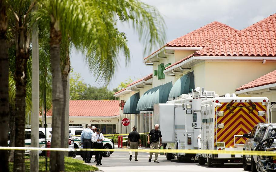 Police gather at the Publix shopping center at the scene of a shooting in Royal Palm Beach, Fla., on Thursday, June 10, 2021.  Authorities say a shooting inside a Florida supermarket has left three people dead, including the shooter.