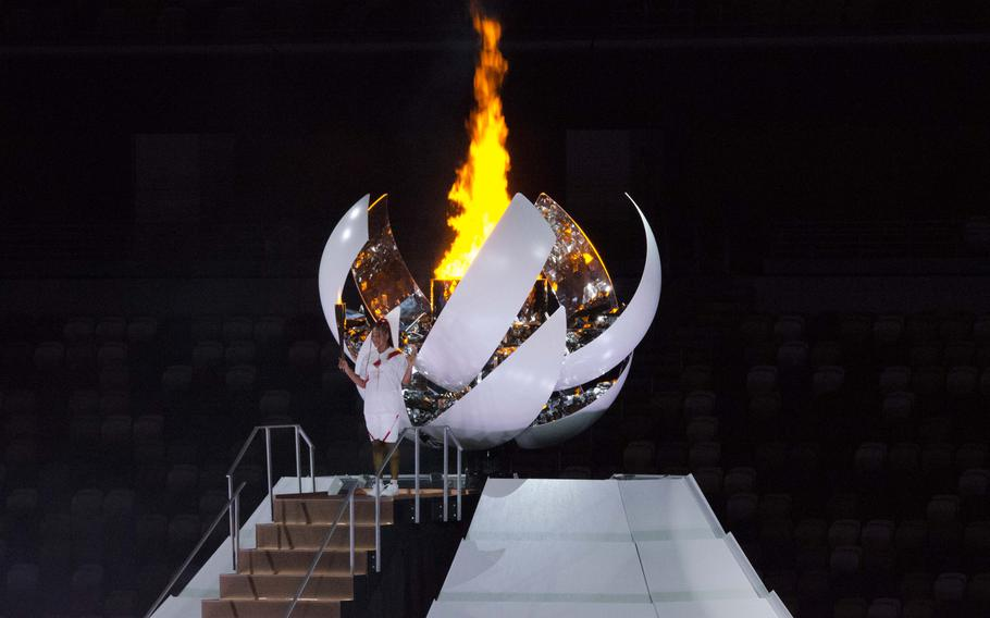 Tennis star Naomi Osaka of Japan stands in front of the Olympic flame after igniting it during the Tokyo 2020 opening ceremony.