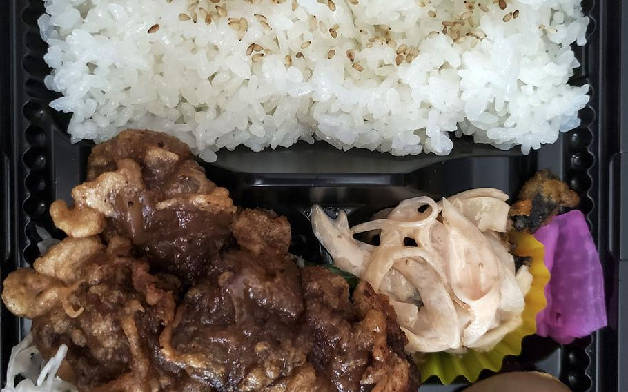Akiruno City Rajikku's whale ginger lunch set comes with a large amount of white rice with pan fried meat on top. A small salad and pickles came with the meal.