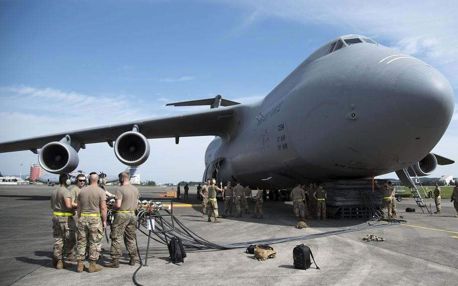 Airmen take part in aircraft recovery training next to a C-5M Super Galaxy visiting Yokota Air Base, Japan, Sept. 13, 2021.