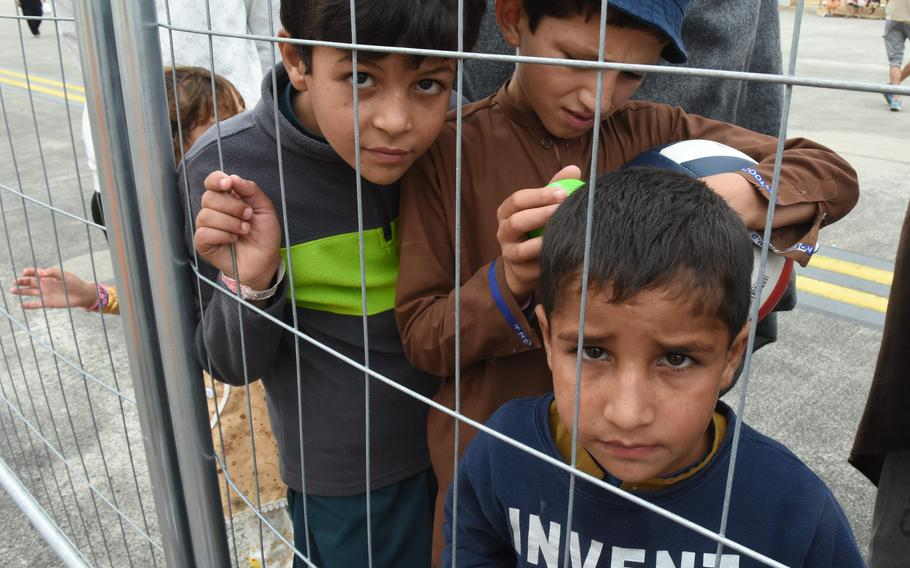 Children stare out from behind a fence inside a temporary living facility on the flight line at Ramstein Air Base, Germany, Aug. 23, 2021. About 7,000 evacuees had arrived by Monday, while some U.S. citizens and families left on flights to the United States.