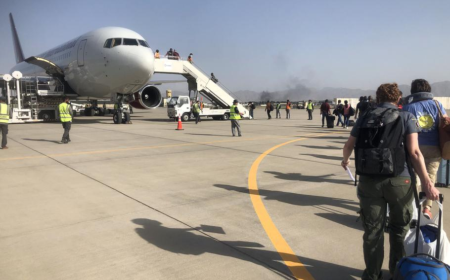 People board a plane chartered by the U.S. government at the airport in Kabul as they prepare to evacuate Afghanistan, Aug. 15, 2021.