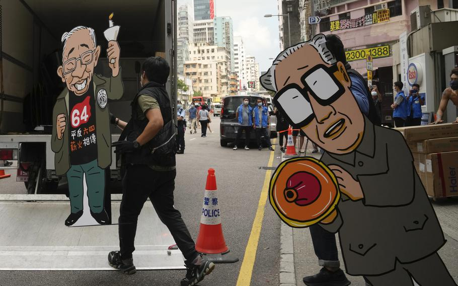 Police officers take away cardboards featuring the images of Former Chinese Premier Zhao Ziyang, right, and pro-democracy activist Szeto Wah from the June 4th Museum in Hong Kong, on Thursday, Sept. 9, 2021. A dozen Hong Kong pro-democracy activists pleaded guilty on Thursday to participating and inciting others to take part in last year's unauthorized candlelight vigil to mark the bloody Tiananmen Square crackdown.