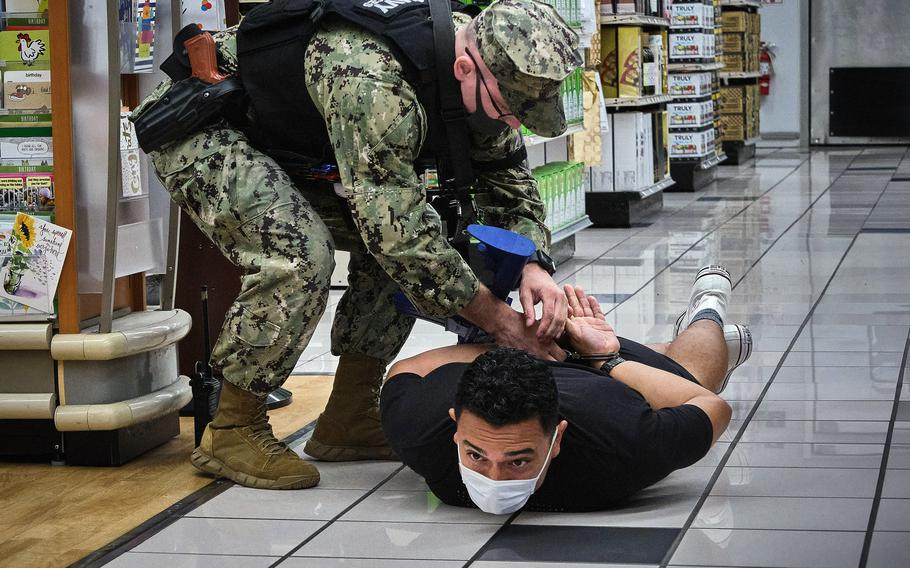 Petty Officer 1st Class James Eggers detains an actor playing an armed suspect during the Citadel Pacific exercise inside the exchange at Yokosuka Naval Base, Japan, July 20, 2021.