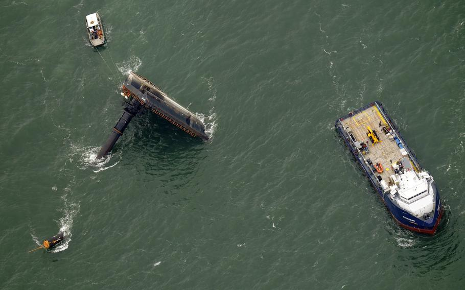 Rescue boats are seen next to the capsized lift boat Seacor Power, left, seven miles off the coast of Louisiana in the Gulf of Mexico on April 18, 2021.