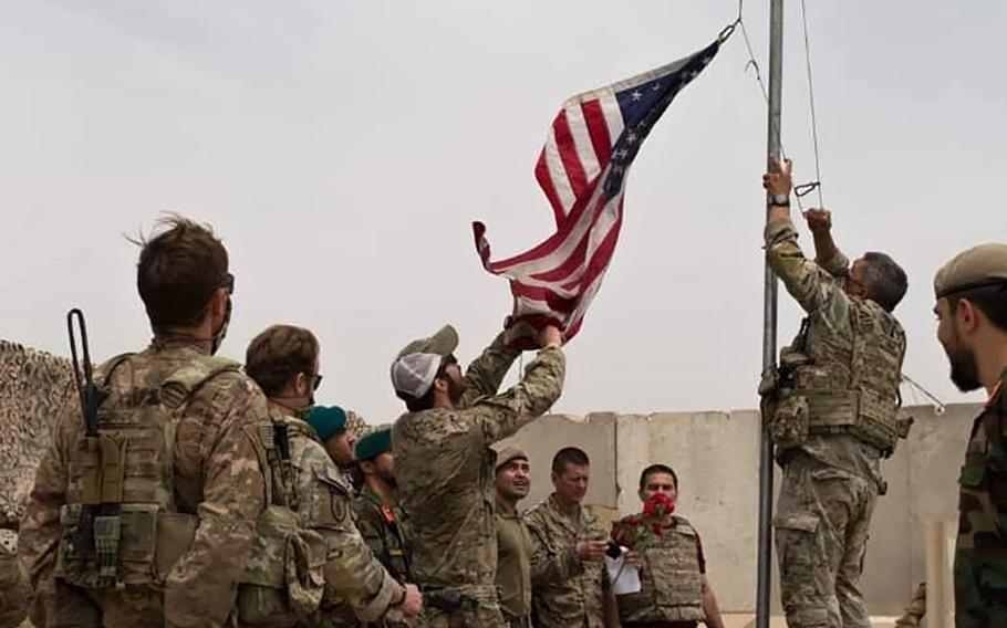 In this May 2, 2021 file photo, a U.S. flag is lowered as American and Afghan soldiers attend a handover ceremony from the U.S. Army to the Afghan National Army, at Camp Anthonic, in Helmand province, southern Afghanistan.