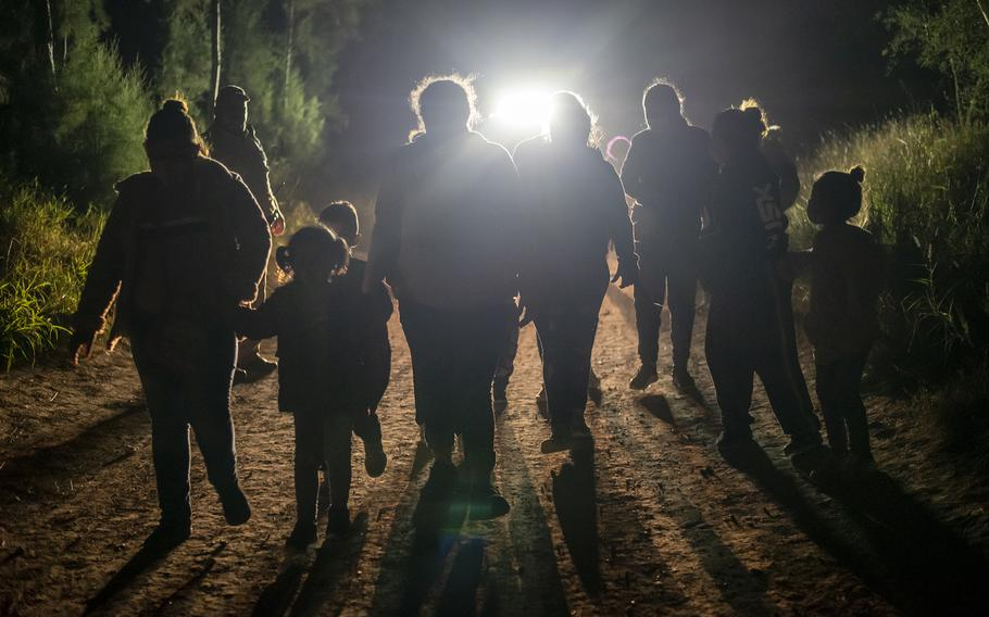 Undocumented immigrants walk toward a Customs and Border Patrol station after being apprehended at the U.S. border near Mission, Texas, on Feb. 10, 2021. Various police departments from around the McAllen area assisted in apprehending unauthorized migrants. Nearly 100 migrants were apprehended in a span of about an hour.