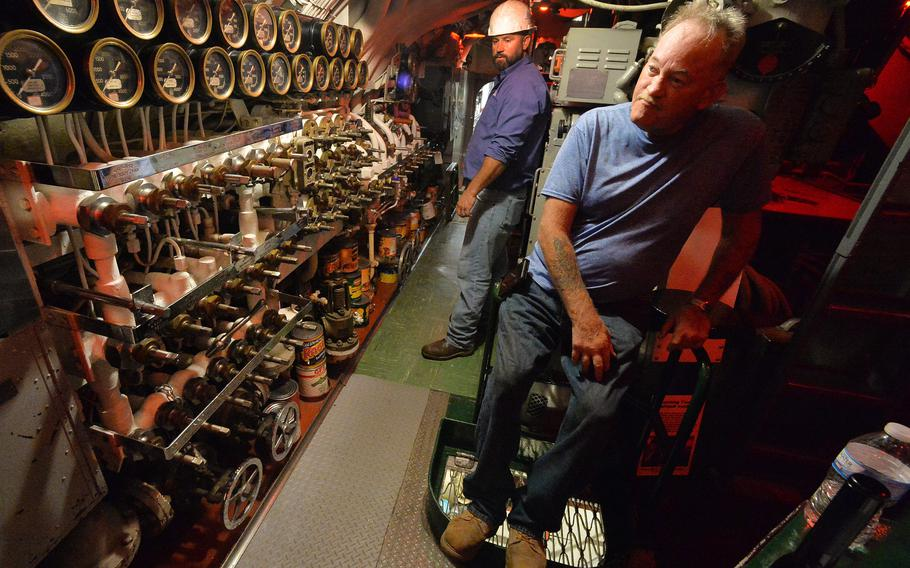 Chief of the boat Darrel Flint, 58, right, pauses while working inside the USS Cod submarine on Aug. 11, 2021, at Donjon Shipbuilding & Repair in Erie. Donjon project manager Matt Ross, 40, is at back. Flint worked on the main air system after a local power outage temporarily stopped repairs.