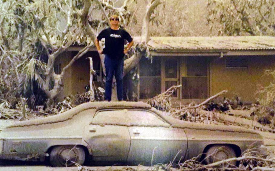 Mark Hanneman, then an agent with the Air Force's Office of Special Investigations, poses on the roof of an ash-covered car at Clark Air Base, Philippines, following the eruption of Mount Pinatubo in June 1991.