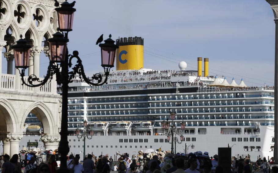 """A cruise ship passes by St. Mark's Square filled with tourists June 2, 2019 in Venice, Italy. Declaring Venice's waterways a """"national monument,"""" Italy is banning mammoth cruise liners from sailing into the lagoon city, which risked within days being declared an imperiled world heritage site by the United Nations. Culture Minister Dario Franceschini said the ban will take effect on Aug. 1 and was urgently adopted at a Cabinet meeting on Tuesday."""