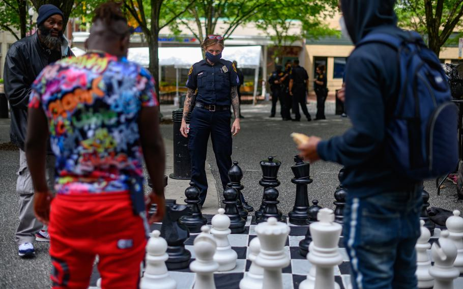 Pittsburgh police Sgt. Tiffany Costa of the Community Engagement Office plays chess with civilians in Market Square.