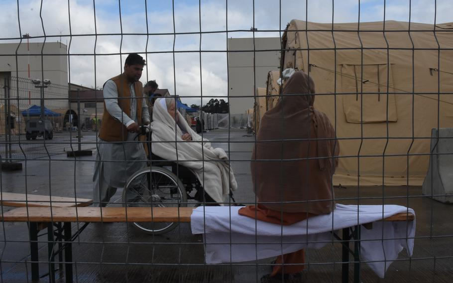 A woman in a wheelchair inside temporary living facilities for evacuees from Afghanistan said Monday, Aug. 23, 2021, that she was an American citizen waiting for transit back to the United States.