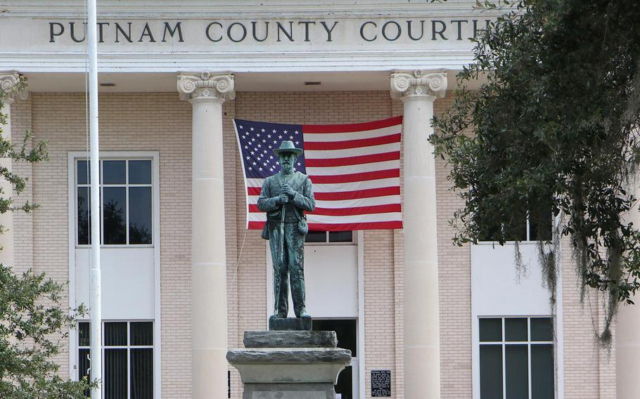A bicyclist rides past the statue of a Confederate Civil War soldier on the grounds of the Putnam County Courthouse in Palatka. This week, the Putnam County Commission will consider an ordinance that would ban the removal of historical landmarks on public property, including the controversial Confederate monument.