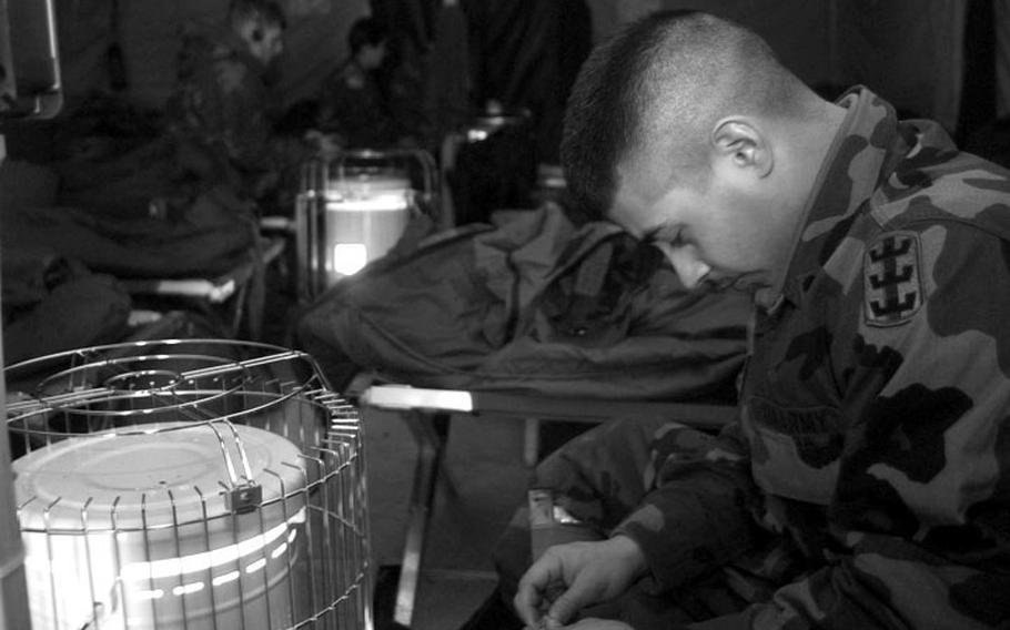 Taszar AB, Hungary, January, 1996: A soldier passes his time reading and staying warm inside his tent before deploying down to Bosnia.