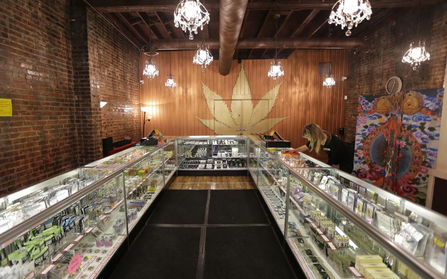 A worker cleans a display case at the Ganja Goddess Cannabis Store in Seattle, on Dec. 7, 2015. Washington state officials announced on June 7, 2021, that the state's nearly 500 licensed marijuana retailers could begin hosting COVID-19 vaccine clinics and offering a single, free pre-rolled marijuana cigarette to any adult over 21 who receives a shot on-site.