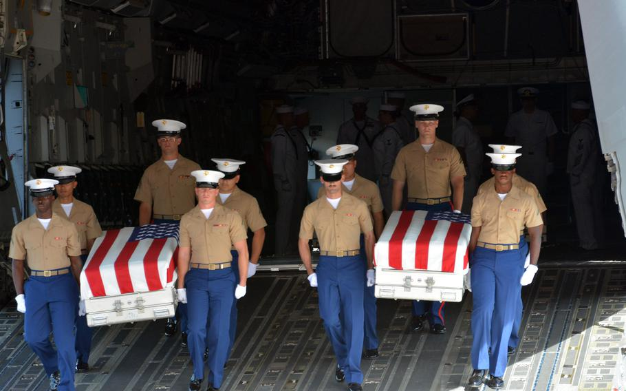 Marines carry coffins from a C-17 during an honorable carry ceremony for the remains of USS Oklahoma service members at Joint Base Pearl Harbor-Hickam, Hawaii, Thursday June 24, 2021.