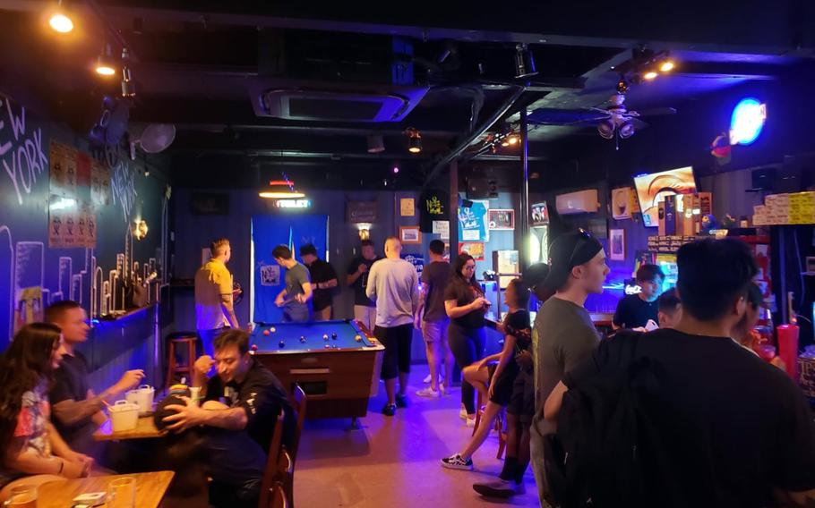 U.S. service members and others hang out at the New York New York Bar and Grill near Yokosuka Naval Base, Japan, Tuesday, June 22, 2021.
