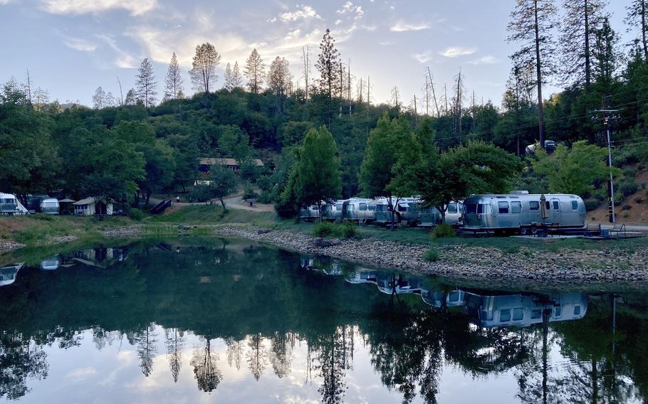 An evening in AutoCamp Yosemite with Airstream trailers settled around the central pond in Midpines, Calif.