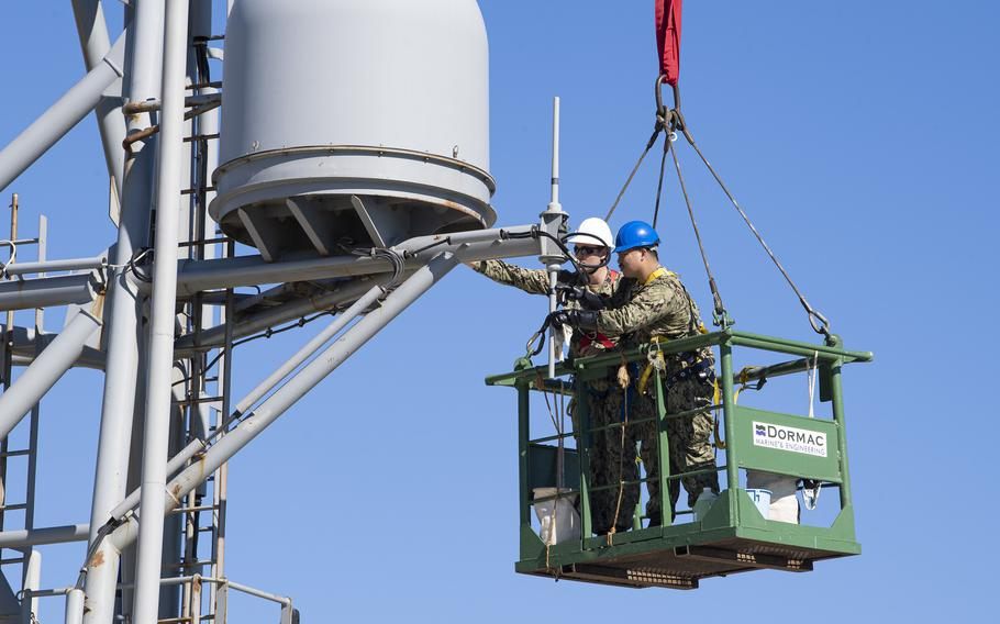 """Petty Officers 2nd Class Nathan A. Milca, right, and Drake W. Childers perform maintenance on the forward house antennae aboard the expeditionary sea base USS Hershel """"Woody"""" Williams while moored in Cape Town, South Africa, for maintenance, Oct. 5, 2021."""