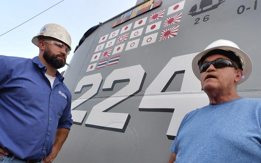 Donjon Shipbuilding & Repair project manager Matt Ross, 40, left, listens as chief of the boat Darrel Flint, 58, describes the enemy flags painted on board the USS Cod on Aug. 11, 2021, in Erie. The floating museum is usually docked in Cleveland and is ending about 6 weeks of steel hull repair and other maintenance.
