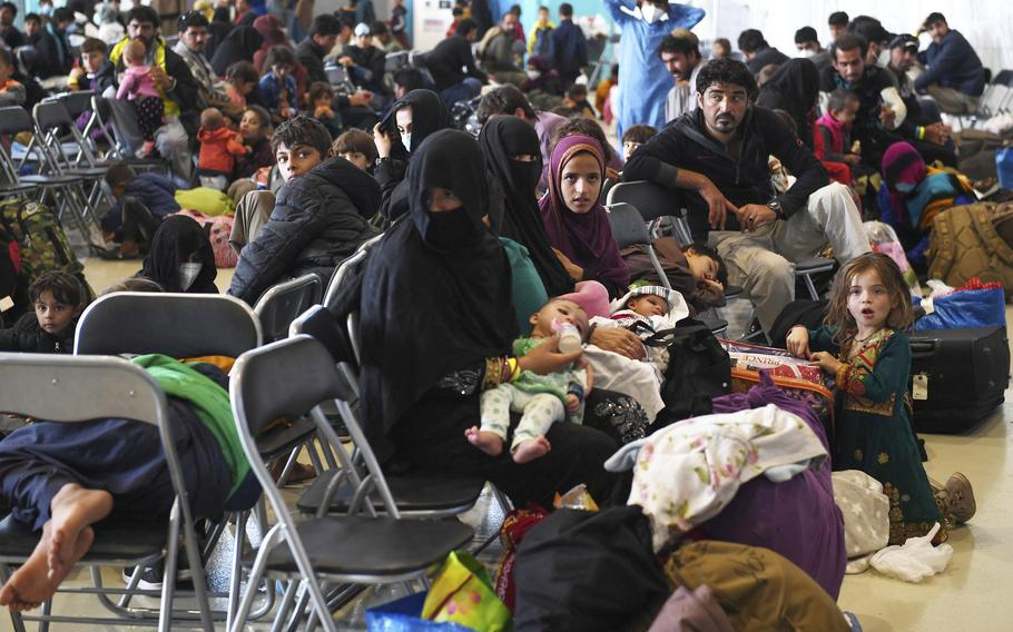 Afghan refugees are seated as they are being processed inside Hangar 5 at Ramstein Air Base in Germany, Wednesday, Sept. 8, 2021. (Olivier Douliery/Pool via AP)