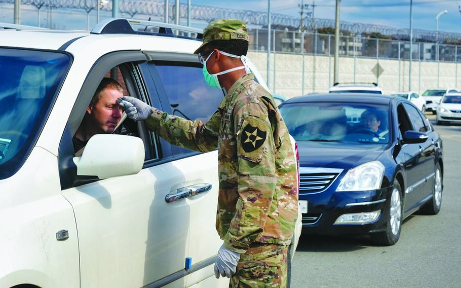A 2nd Infantry Division soldier checks for a temperature at Camp Humphreys, South Korea, Feb. 26, 2020.