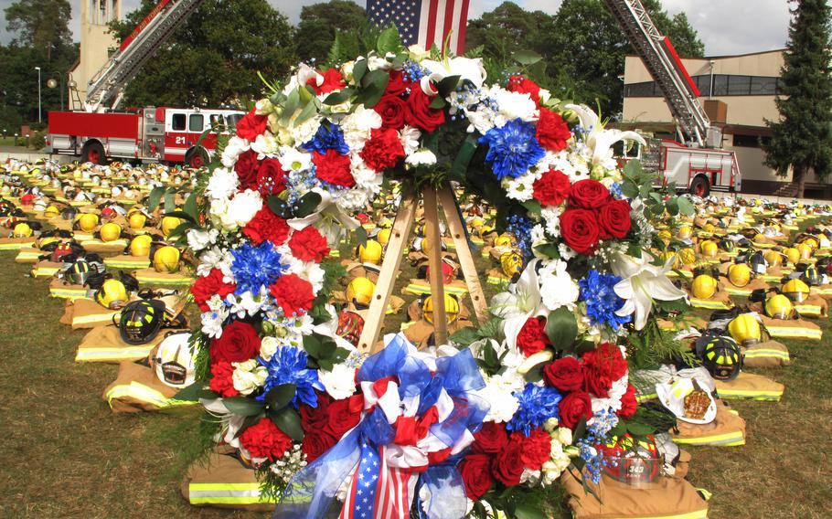 A wreath laid by service members at Ramstein Air Base sits in front of hundreds of firefighters' helmets and protective gear during a ceremony on Sept. 10, 2021, to mark the 20th anniversary of the 9/11 attacks on the U.S.