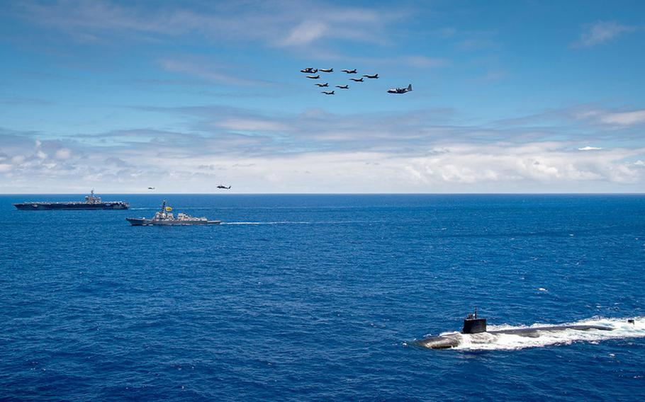 The aircraft carrier USS Carl Vinson, guided-missile destroyer USS Dewey and attack submarine USS Seawolf sail in formation near Hawaii while Marine Corps aircraft fly overhead, June 22, 2021.