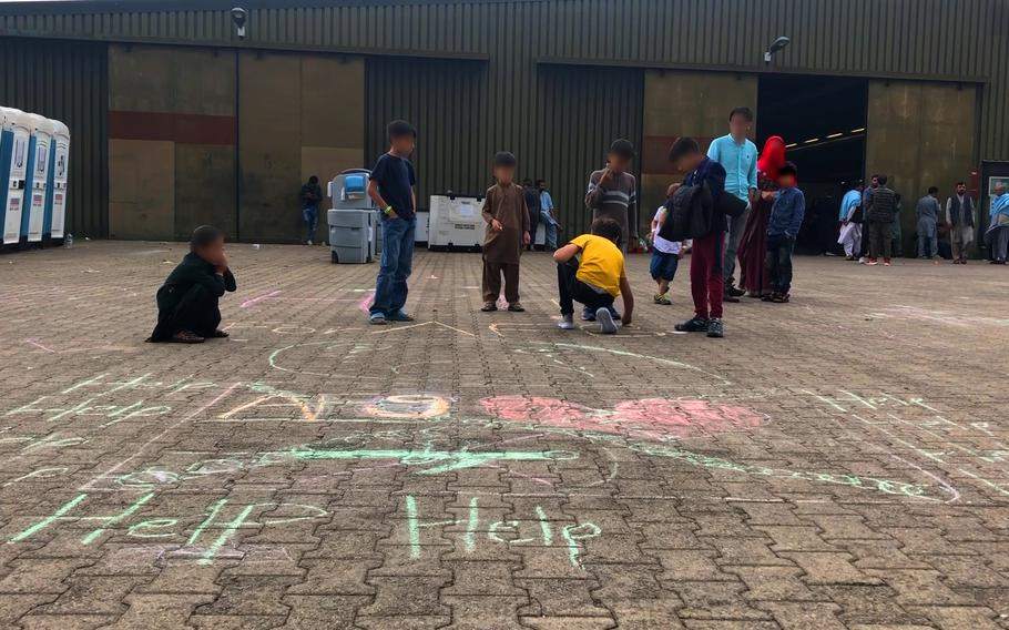 """Afghan boys draw the word """"help"""" and a broken heart with chalk on paving slabs at Rhine Ordnance Barracks in Kaiserslautern, Germany, Aug. 30, 2021. The children's faces have been blurred to protect anyone they may have left behind in Afghanistan."""