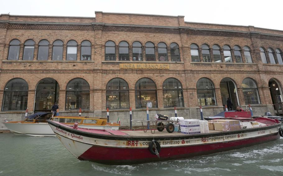 A boat sails past a historical artistic glass factory in Murano island, Venice, Italy, Thursday, Oct. 7, 2021.