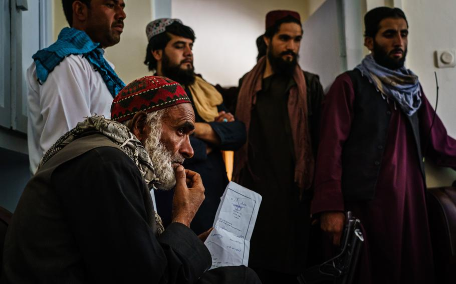 Several men sit in waiting to solve legal disputes in the ground-floor office of Abdul Qadeer Shahadatyar, a Taliban judge stationed in PD10, in Kabul, Afghanistan, Thursday, September 2, 2021.