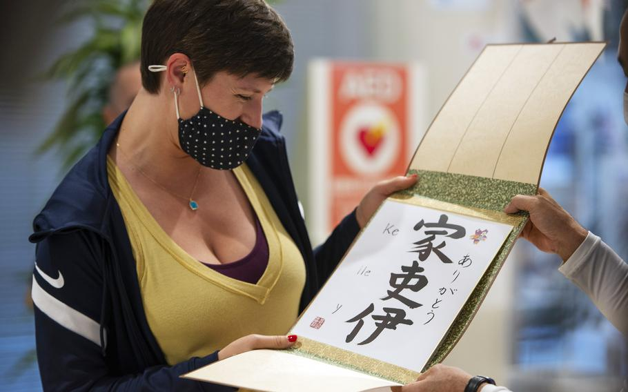 Kelley Hurley of the U.S. women's Olympic team accepts gifts from the city of Iwakuni, Japan, Tuesday, July 13, 2021. Each athlete's name was written in Japanese kanji calligraphy.