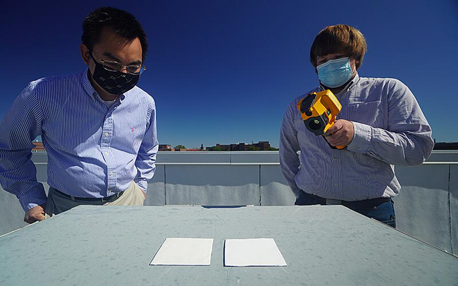 Purdue researchers Xiulin Ruan, left, and Joseph Peoples use an infrared camera to compare the cooling performance of white paint samples on a rooftop.