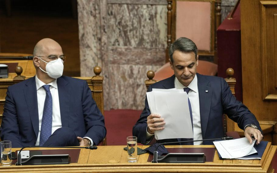 Greek Prime Minister Kyriakos Mitsotakis, right and and Greek Foreign Minister Nikos Dendias take part in a parliament session in Athens, Thursday, Oct. 7, 2021. Greece's lawmakers are debating and voting on a broad five-year defense pact signed last week with France which includes a clause of mutual assistance in case of attack by a third party. Prime Minister Kyriakos Mitsotakis signed the deal with French President Emmanuel Macron during a Sept. 28 visit to Paris.