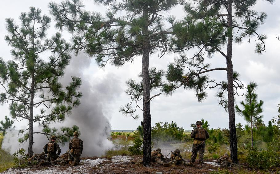 A claymore mine blast sends smoke in the air as Marine infantry students open fire from a tree line on Camp Lejeune, N.C., training grounds on Aug. 27, 2021. The students were practicing an ambush during an initial infantry training pilot program meant to drastically change the way the Corps trains its infantrymen. The pilot program expands infantry training from nine to 14 weeks and places Marines in 14-person squads under a single instructor.