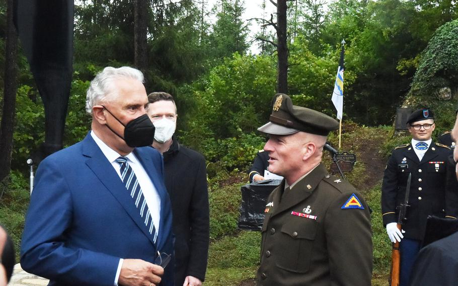 Bavaria's Interior Minister, Joachim Herrmann, left, speaks with Brig. Gen. Joseph Hilbert, commander of the 7th Army Training Command, right, during the 50th anniversary ceremony for the Pegnitz helicopter crash on Aug. 18, 2021, near Pegnitz, Germany.