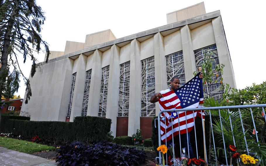 FILE-In this Oct. 27, 2019 file photo a man places an American flag outside the Tree of Life synagogue in Pittsburgh on the first anniversary of the shooting at the synagogue, that killed 11 worshippers. An evidentiary hearing in the case of Robert Bowers a western Pennsylvania truck driver accused of killing 11 people at the Pittsburgh synagogue in 2018, is expected to get underway inside a federal courtroom in Pittsburgh on Tuesday, Oct. 12, 2021.