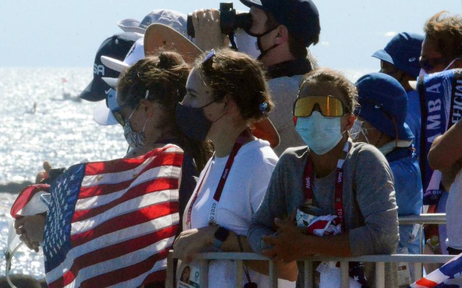 Lt. j.g. Nikki Barnes, in dark mask, the first U.S. Coast Guardsman to represent the United States at the Olympics, watches the men's 470 race from Enoshima, Japan, Wednesday, Aug. 4, 2021.