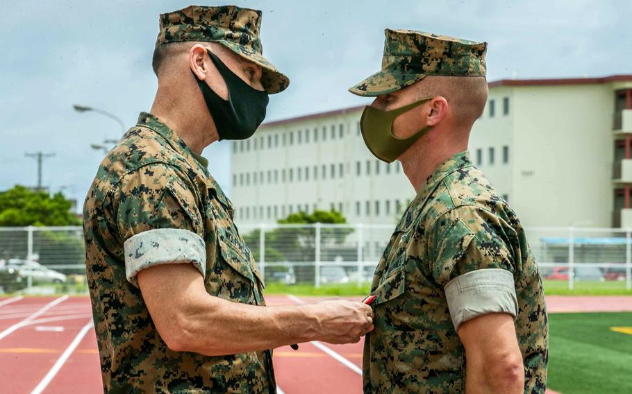 Brig. Gen. Brian Wolford, commander of the 3rd Marine Logistics Group, awards a Navy and Marine Corps Medal to Sgt. Maj. David Potter of the 9th Engineer Support Battalion at Camp Hansen, Okinawa, Aug. 2, 2021. Potter was honored for saving a woman and her child from drowning during a flash flood last year.