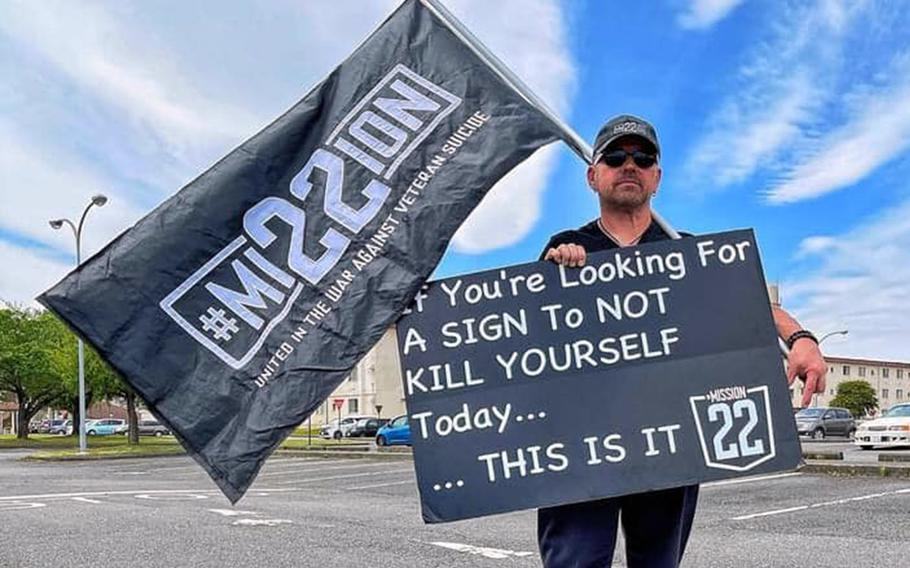 """Air Force veteran Scot Northcutt often stands on Yokota Air Base, Japan, holding a sign with a jarring message: """"If you are looking for a sign to not kill yourself today, this is it."""" He spreads his message on behalf of Mission 22, an organization aimed at bringing awareness to veteran suicide."""