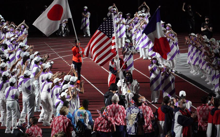The flags of Japan, the United States and France are carried into National Stadium during closing ceremonies for the Tokyo Paralympics, Sunday, Sept. 5, 2021.